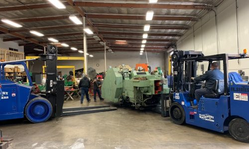 Two Forklifts moving CNC equipment